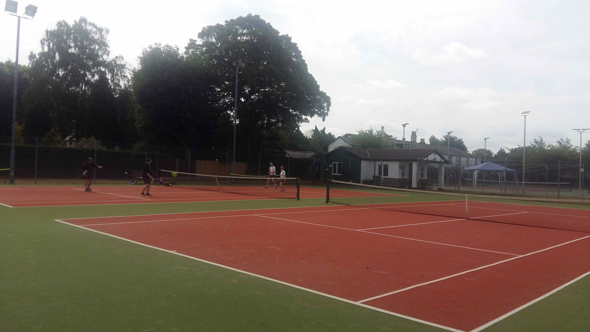 People playing tennis at the Club