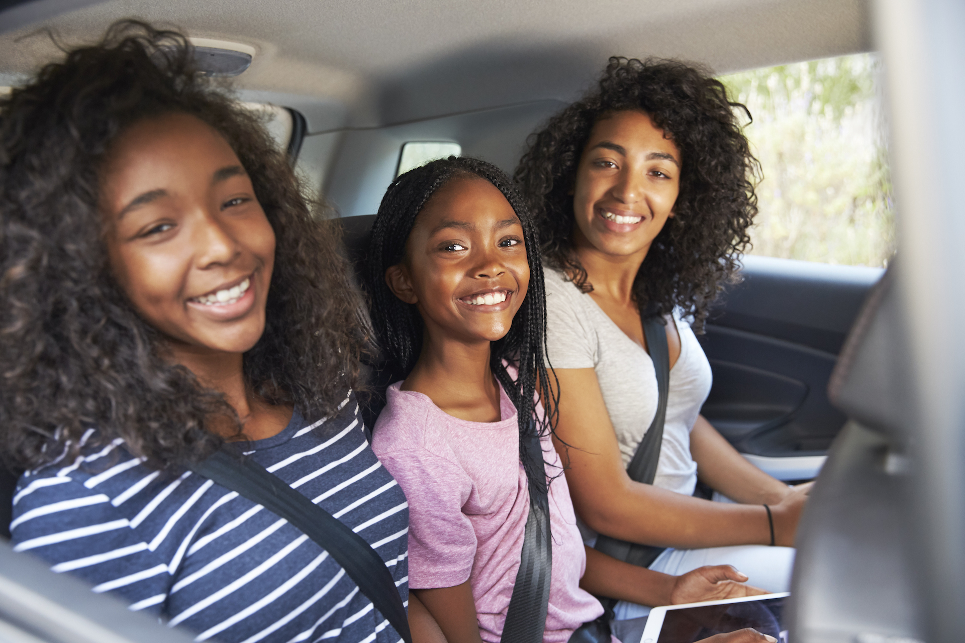 portrait-of-family-with-teenage-children-in-car-PZ2U9WC.jpg