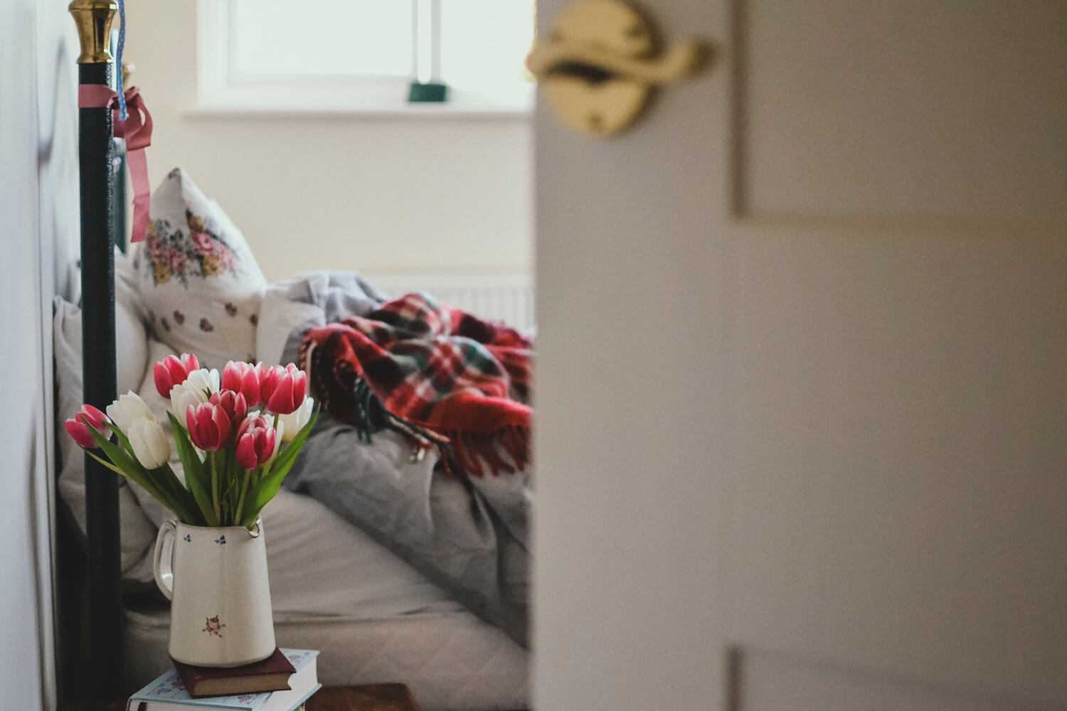 A cosy bed with blanket and bunch of tulips - Time management tips for creatives