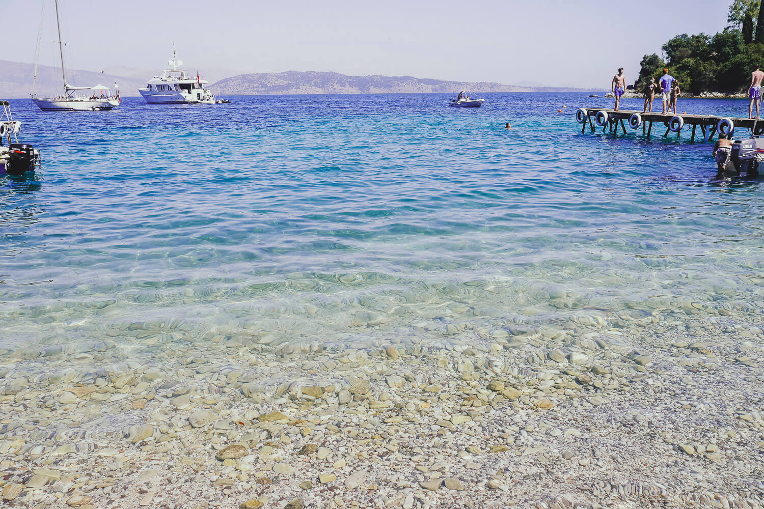 A pebbly beach in Corfu on a hot summer's day - how to take a holiday as a designer or maker