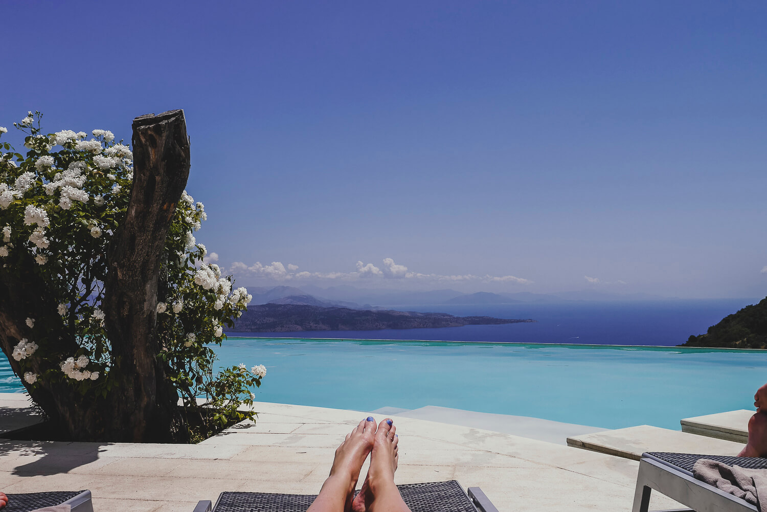 relaxing on a sun lounger on the edge of a pool - The Rou Estate Corfu