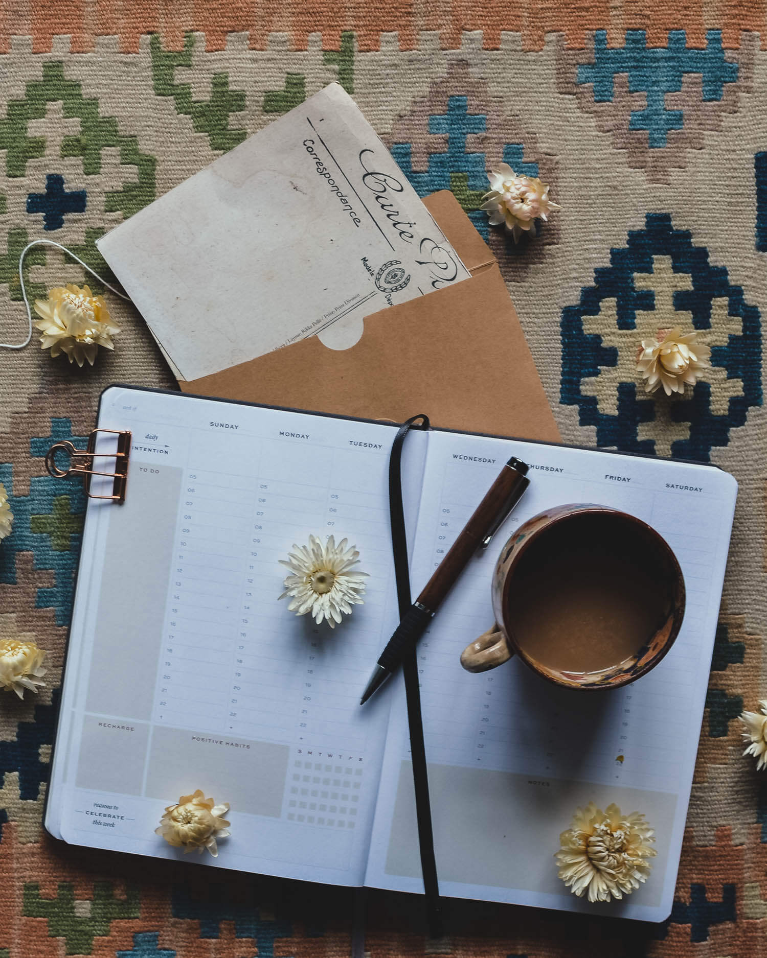 Diary on a rug with dried flowers and vintage postcard