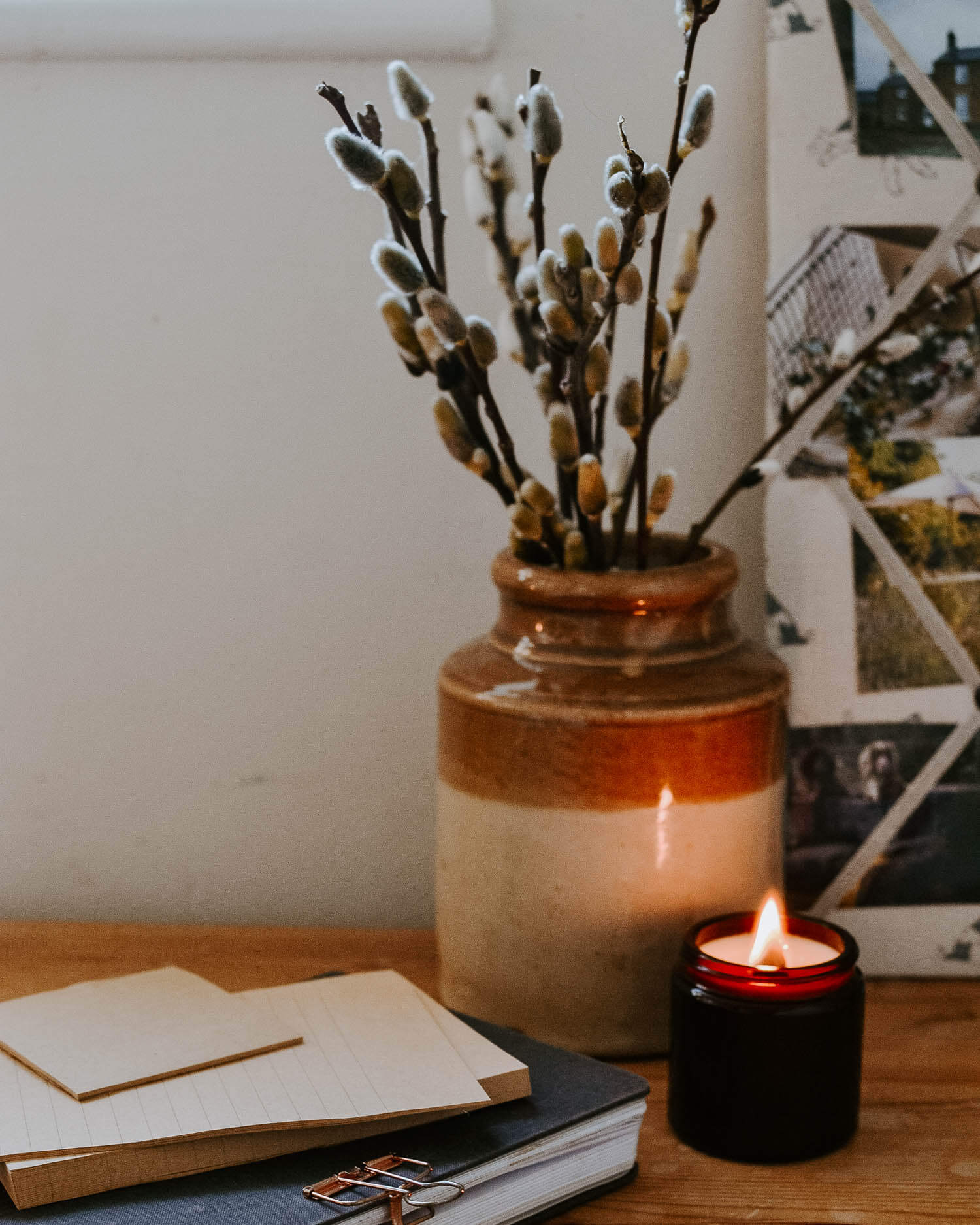 Spring willow blossom and a lit candle on a wooden desk