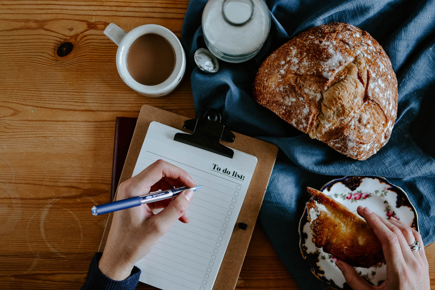 Writing a to-do list at a breakfast table with sourdough and a cup of tea