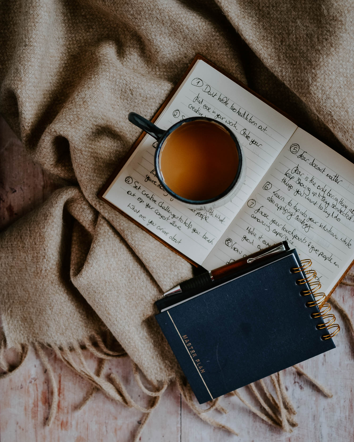 Notebooks and a cup of tea on a blanket | Josephine Brooks