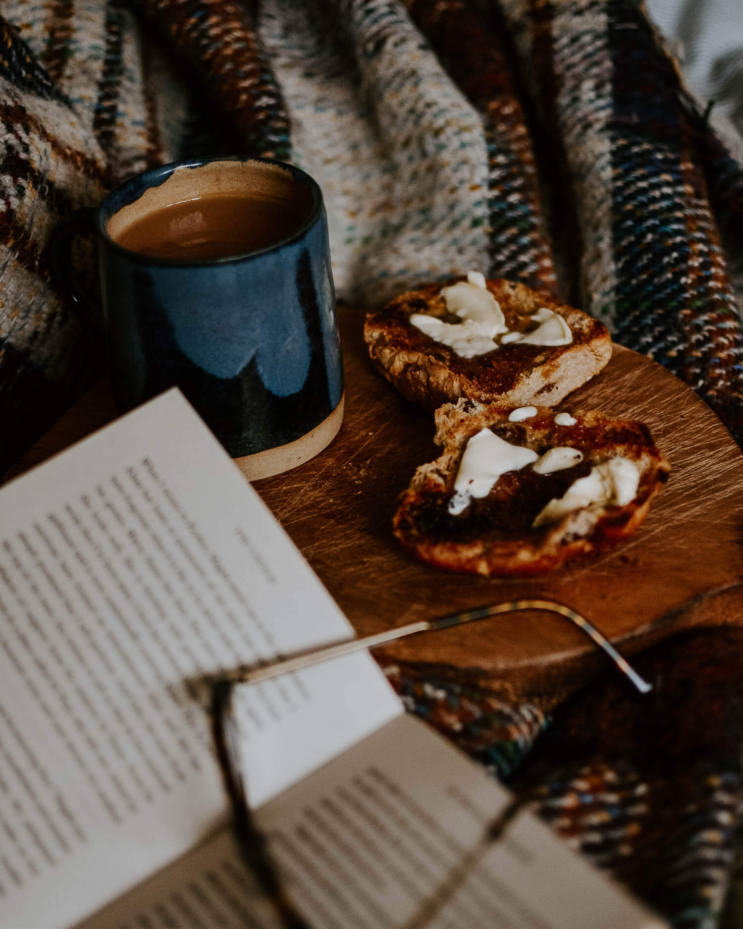 Hot cross buns with butter melting on a wooden board with a cup of tea - reading in bed | Josephine Brooks