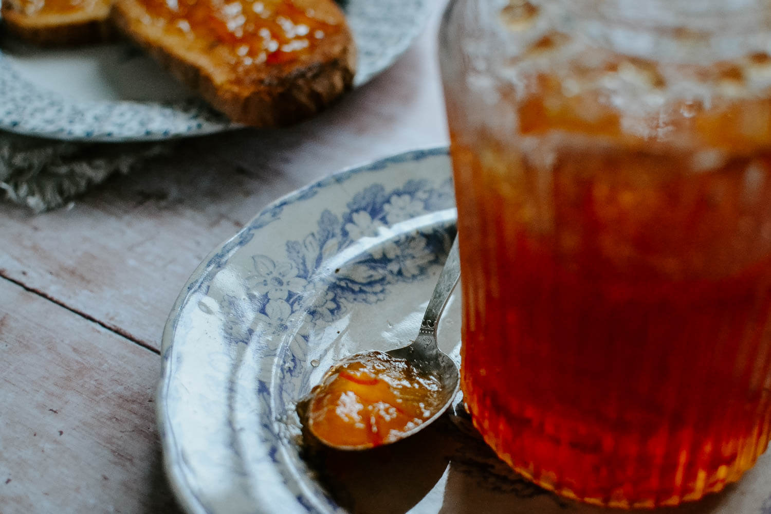 Large jar of orange marmalade on a rustic table with vintage china plates