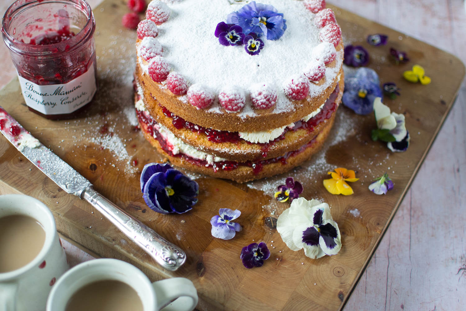 Victoria Sponge Cake with Flowers and cups of tea