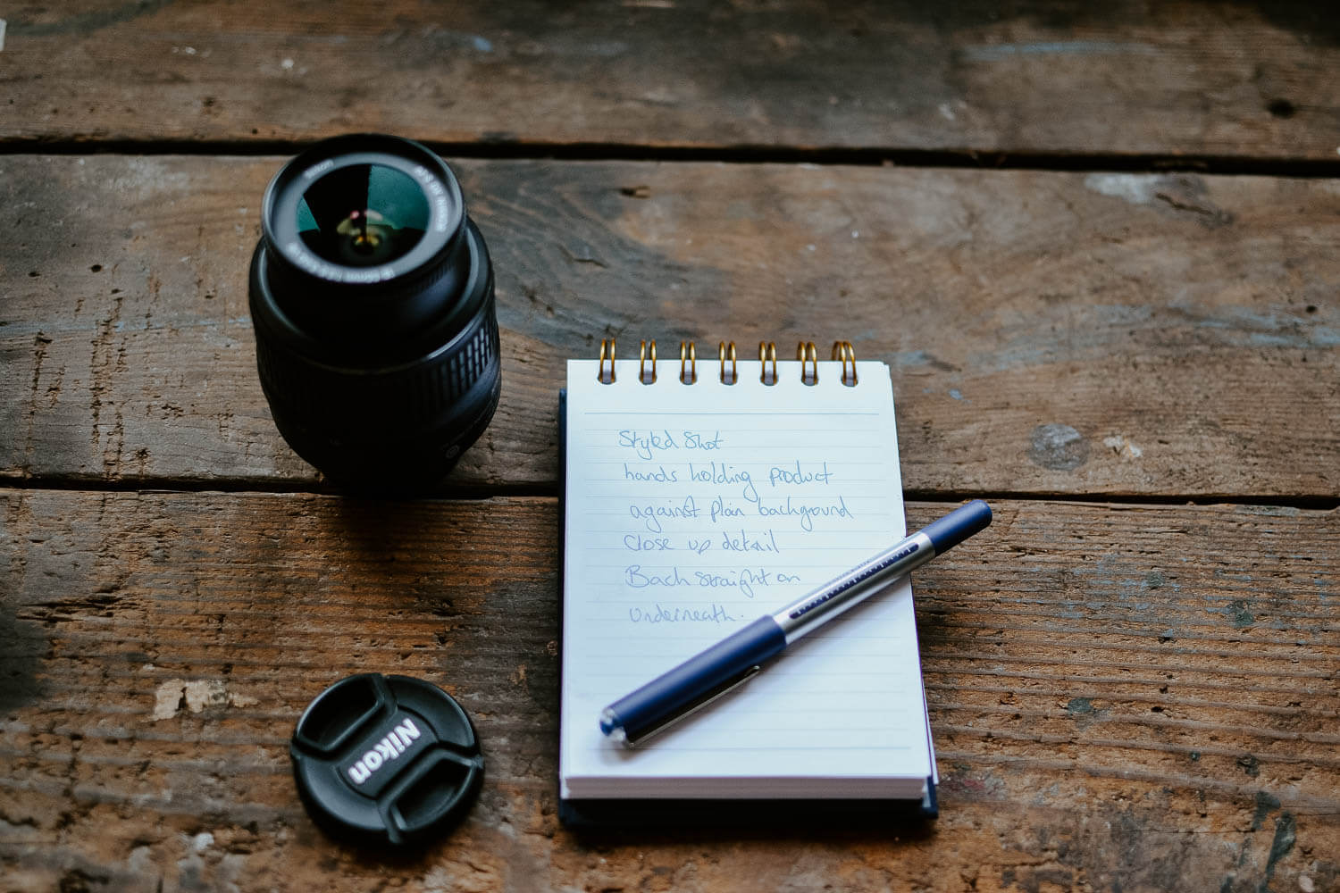 Camera lens and lens cap on rustic wooden table