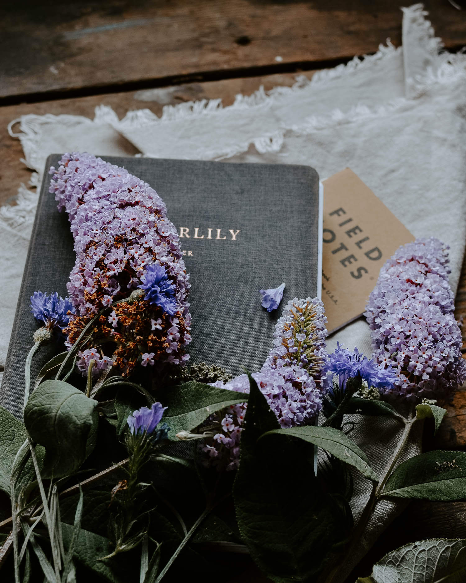 Summer flowers on a notebook onto of a rustic wooden table | Josephine Brooks