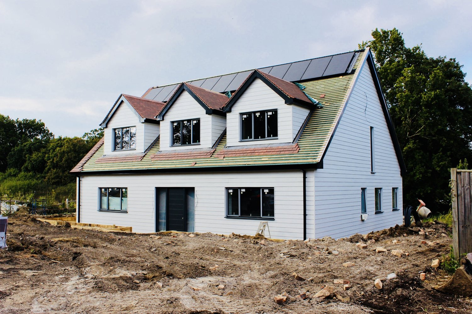 The roof tiles and solar panels being installed on the exterior of a eco home In West Sussex