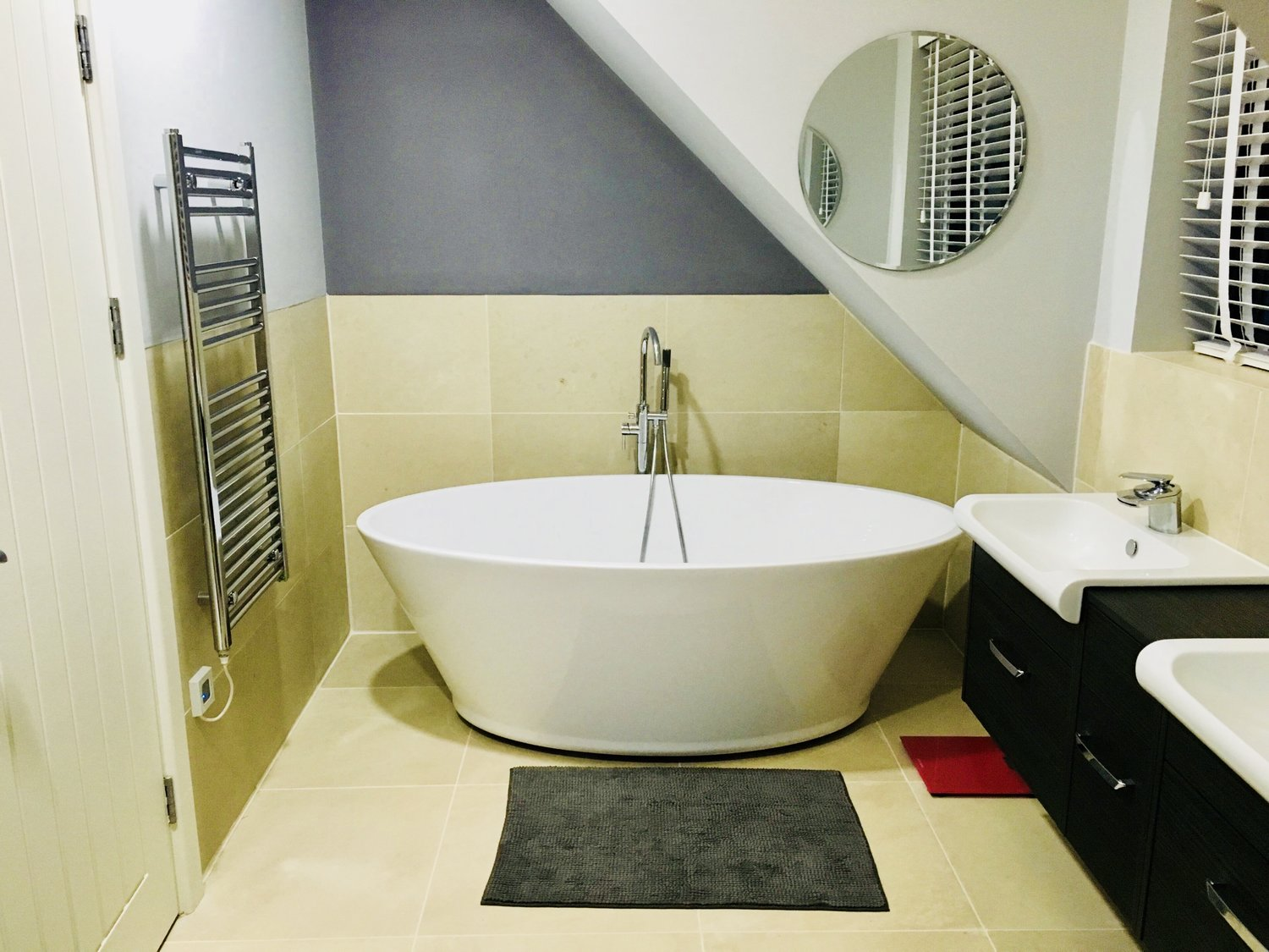 Vessel bowl bath, towel radiator, and a floating double sink for a sophisticated modern look for a eco home in West Sussex.