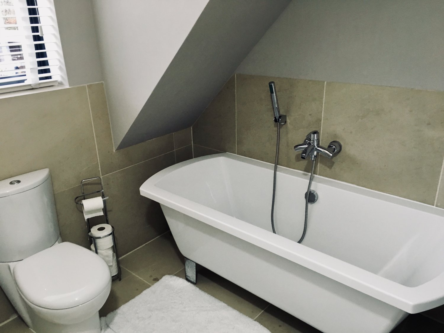 The family bathroom showing a floating bath and a toilet for a eco home in West Sussex
