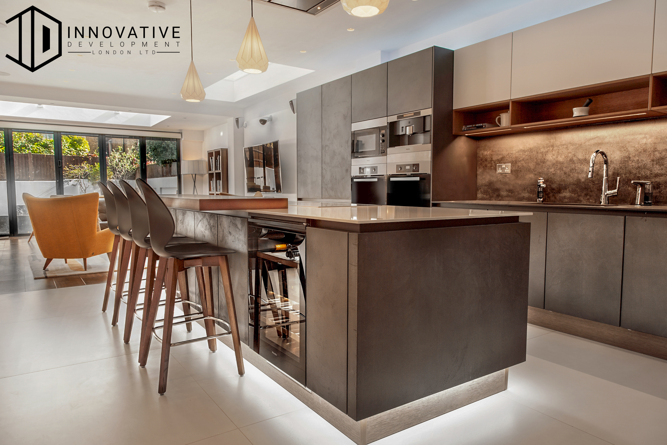 Whole view of a Stunning modern Kitchen with a combined Living room area with a creamy interior design for a completed Kitchen extension in Chiswick