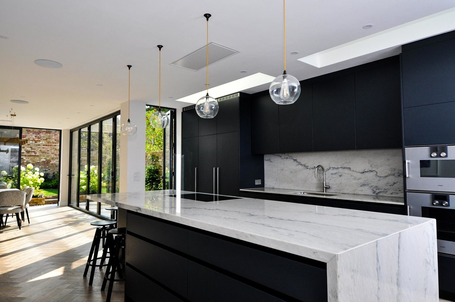 Beautiful kitchen and living room with marble worktops and a modern interior design for a completed Kitchen Extension in West Hampstead