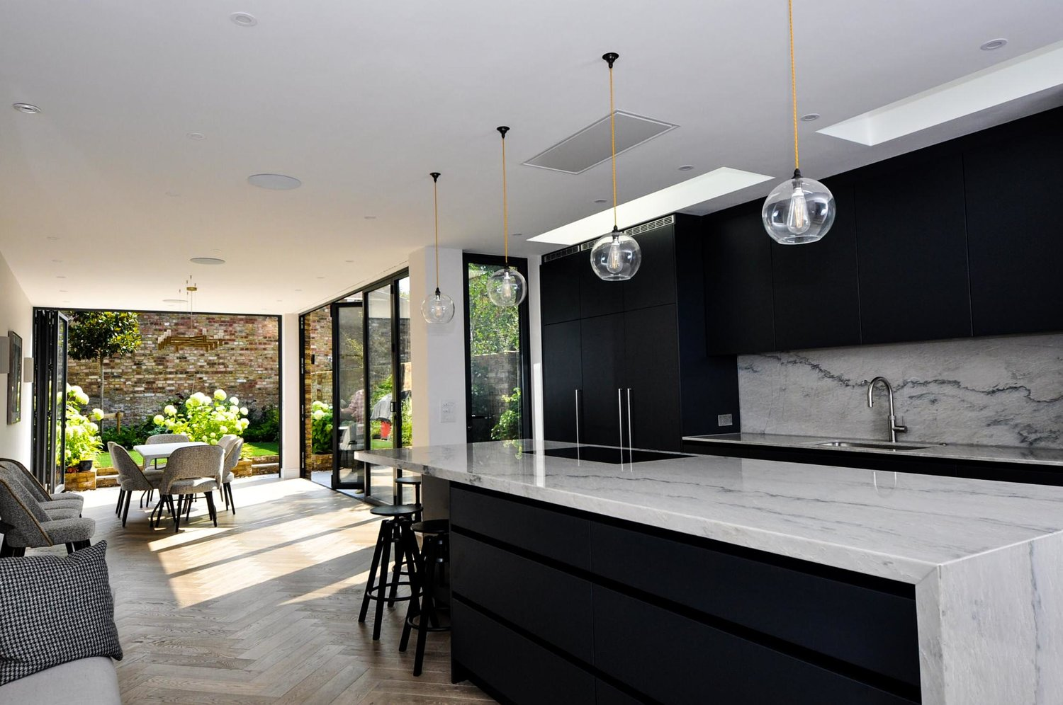 The whole overview of a beautiful kitchen and living room with marble worktops and a modern interior design for a completed Kitchen Extension in West Hampstead