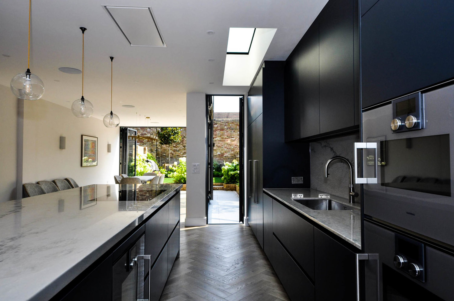 Beautiful and spacious kitchen work space with marble worktops and a modern interior design for a completed Kitchen Extension in West Hampstead