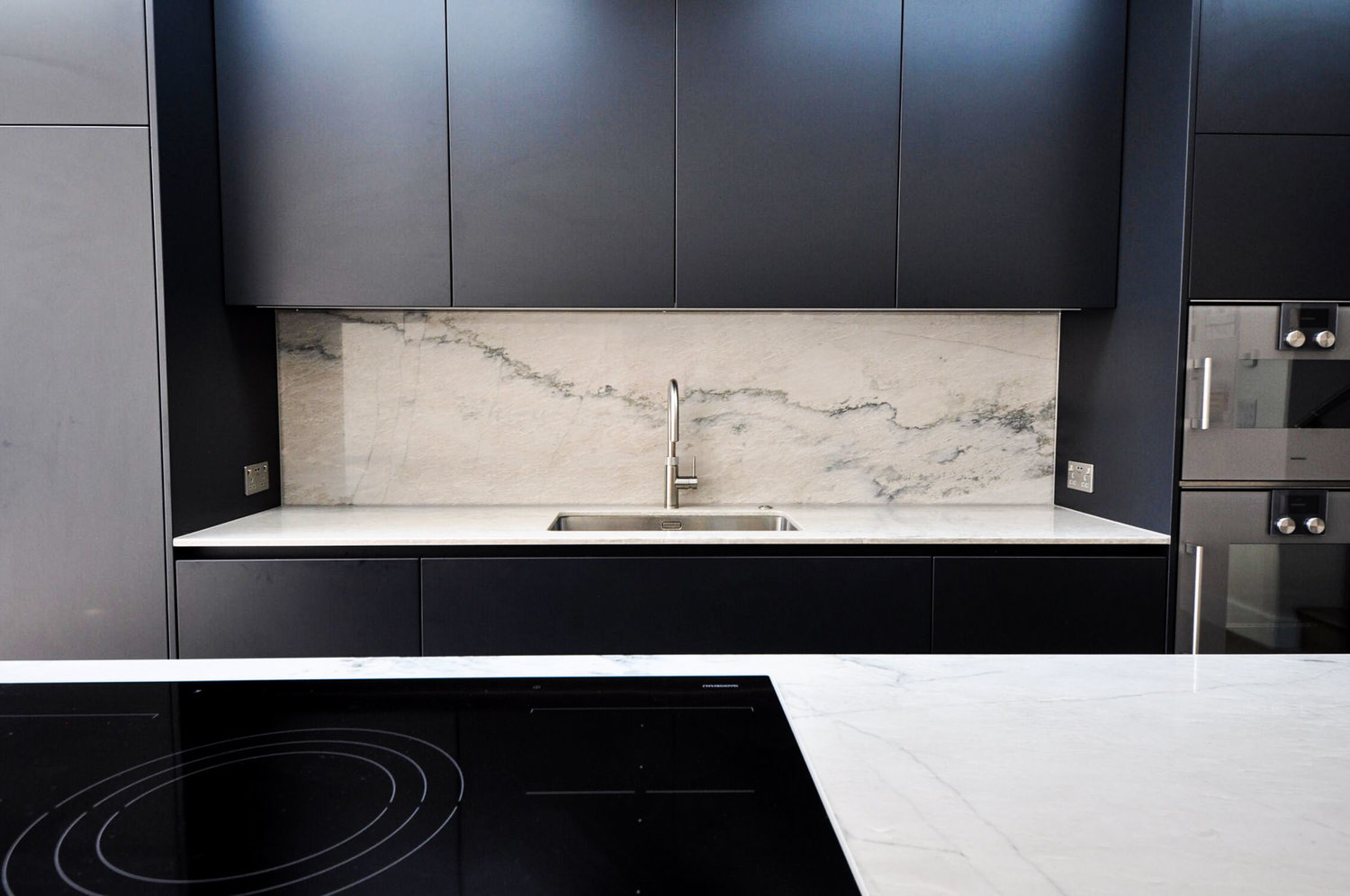 The electric induction hob on a kitchen island, and kitchen sink with marble worktops that create a modern interior design for a completed Kitchen Extension in West Hampstead
