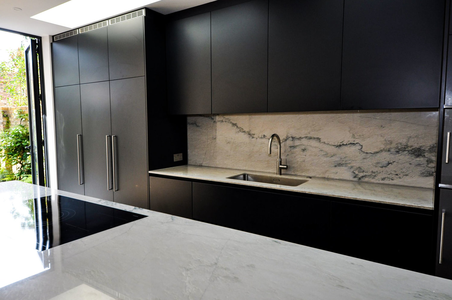 The electric induction hob on a kitchen island, and kitchen sink with marble worktops that create a modern interior design that's naturally lit for a completed Kitchen Extension in West Hampstead