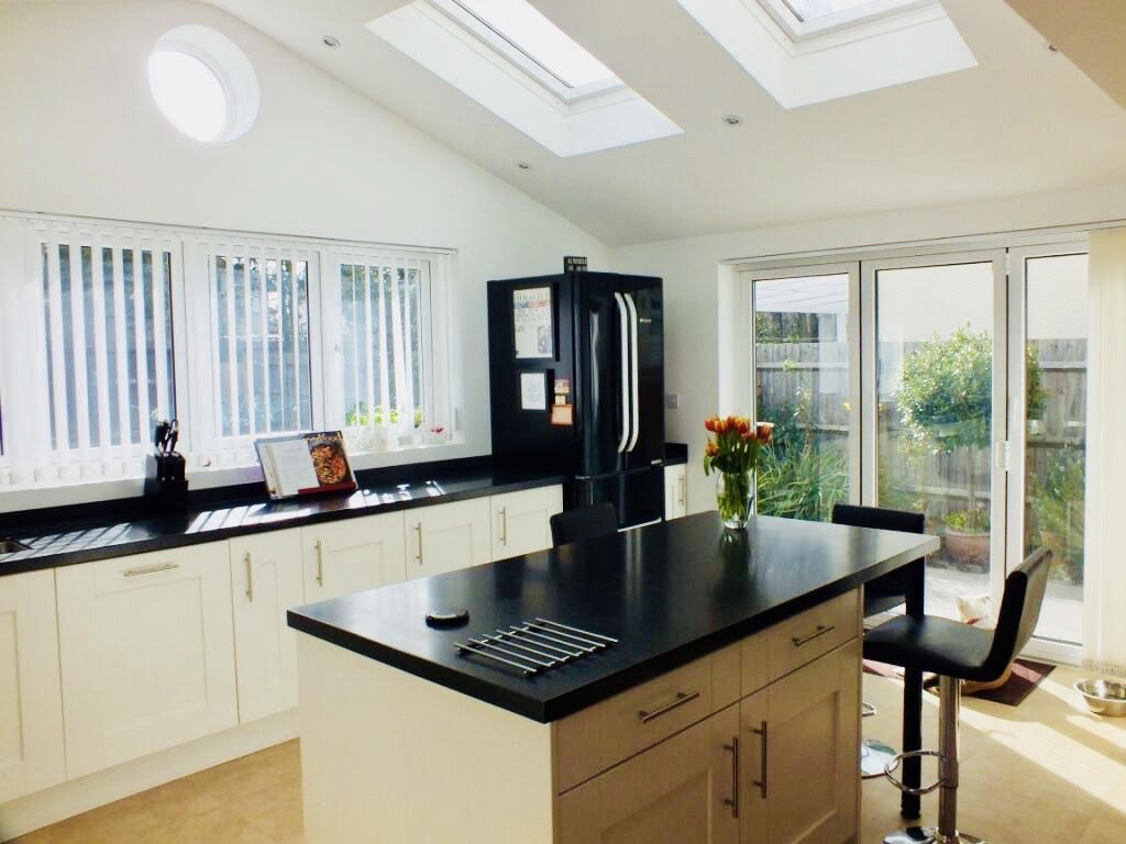 Stunning naturally lit kitchen with skylights, bulls-eye window, picture window and bi folding doors for a completed Kitchen extension in Surbiton