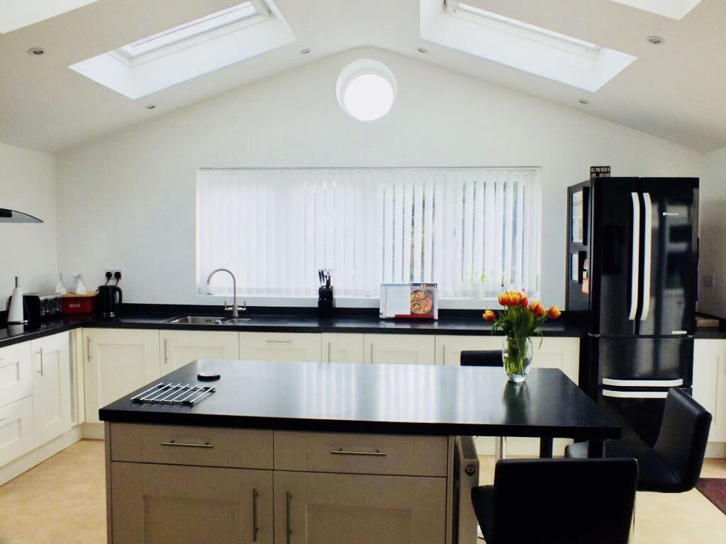 Full overview of a stunning naturally lit kitchen extension, with a bulls-eye window, picture window and bi folding doors for a completed Kitchen extension in Surbiton