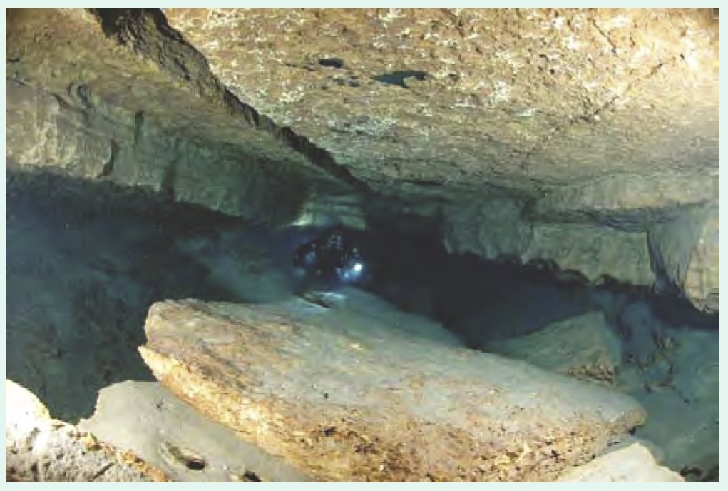Jacobs Well Spring: Photograph showing the karst enlarged fracture routing groundwater to the surface. If you click on the photo to enlarge, you will be able to see the diver in the center of the photo shining a light. A good reference for the size of the cavern.