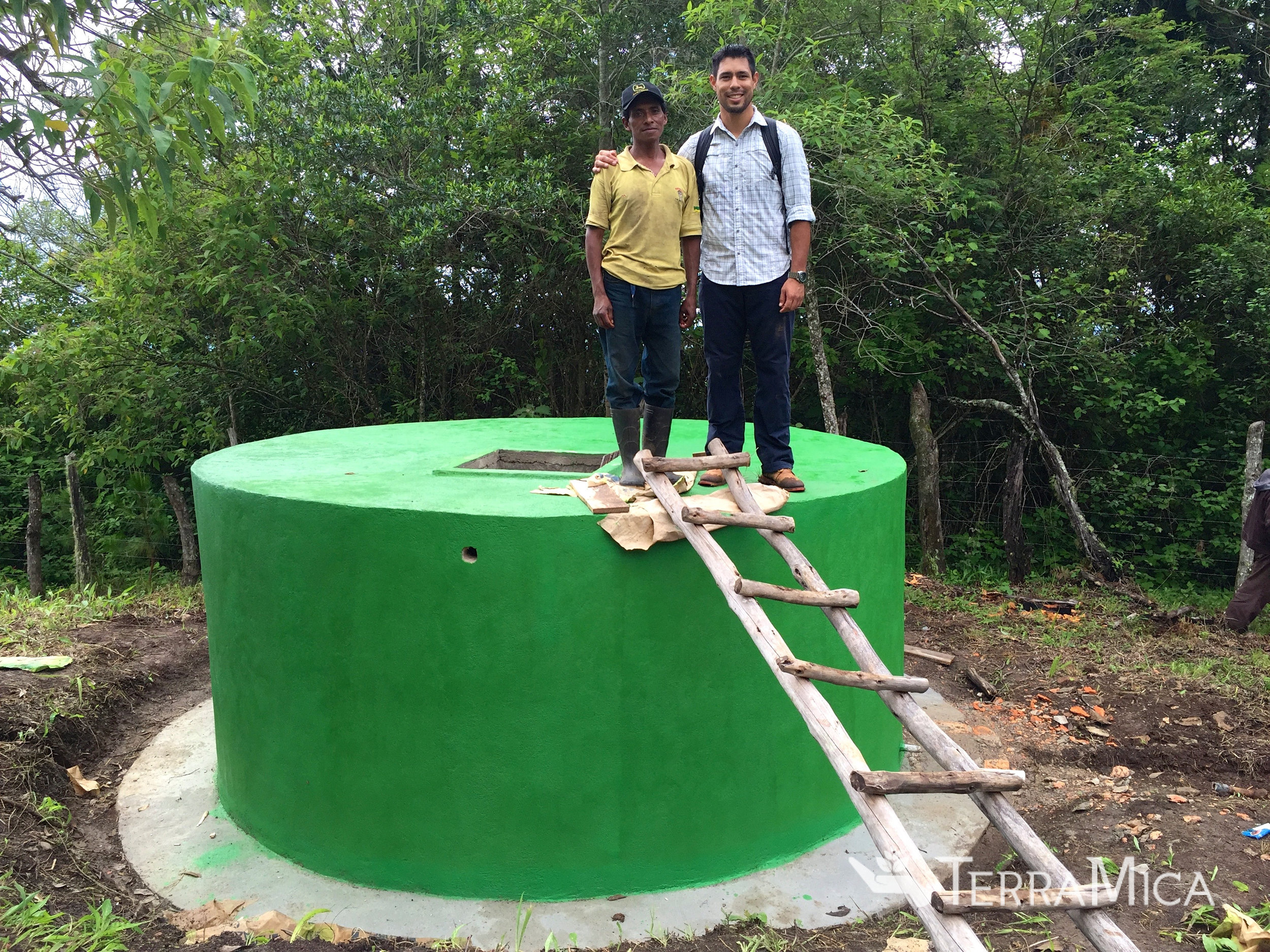 Jorge on water tank with a local man who participated in the restoration work with TerraMica.