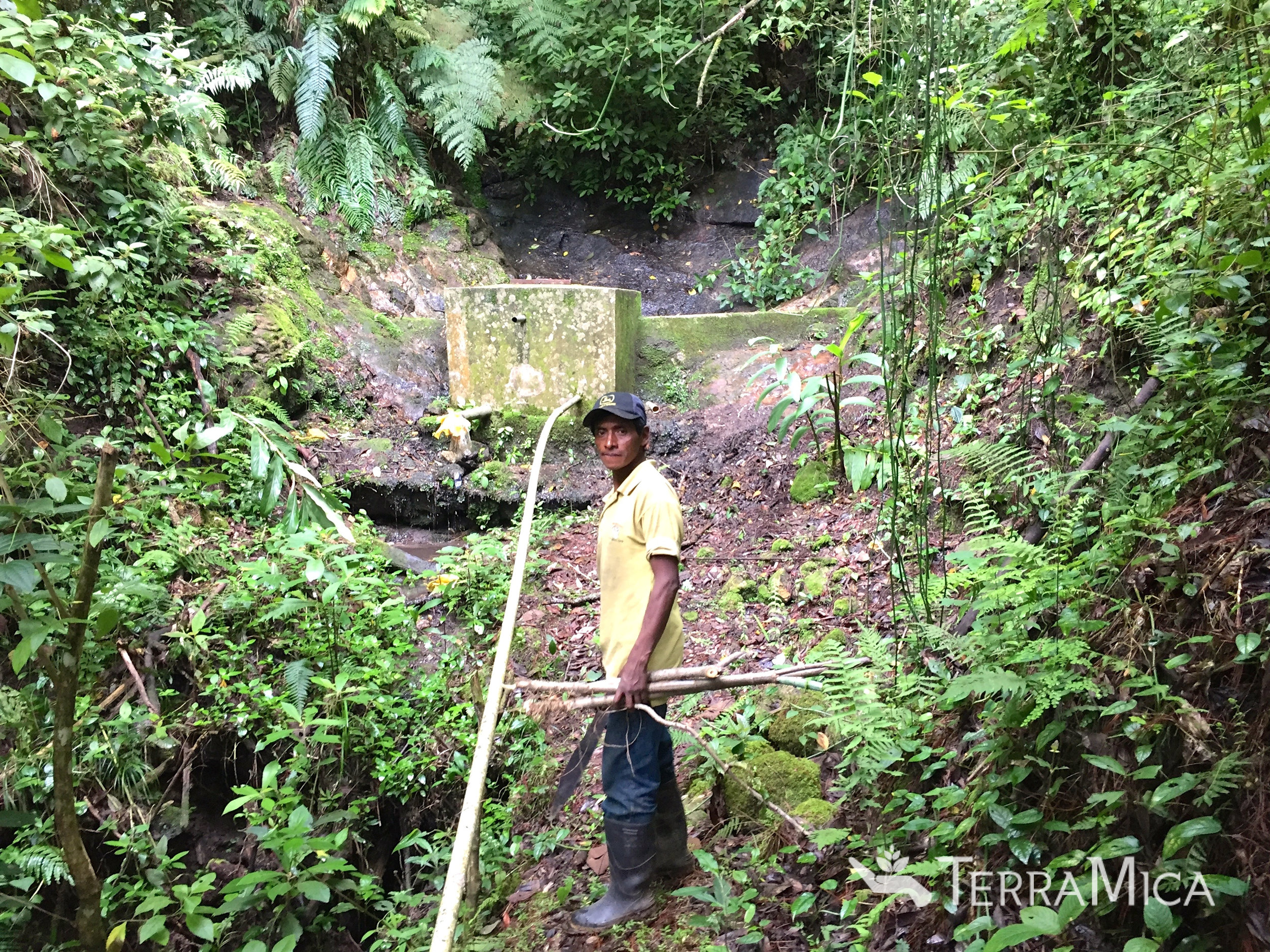 Local villager working with TerraMica on the pipe repair from the water source to the reservoir.