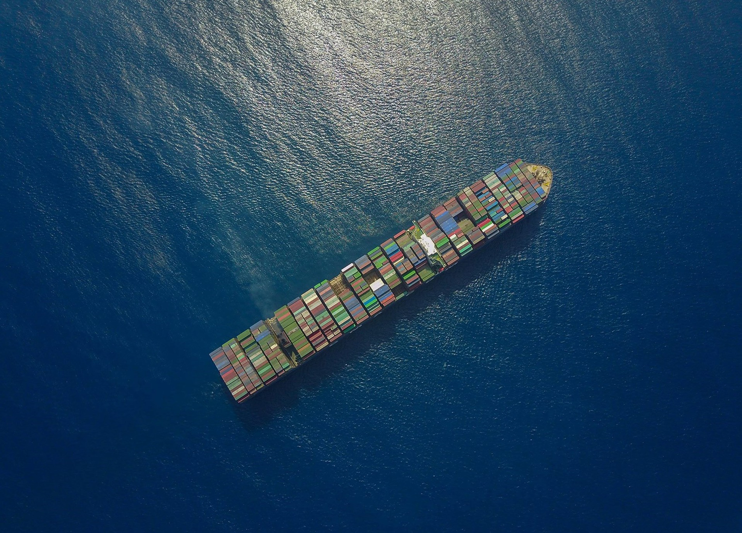 aerial-view-ocean-shipping-container-alexander-unsplash.png