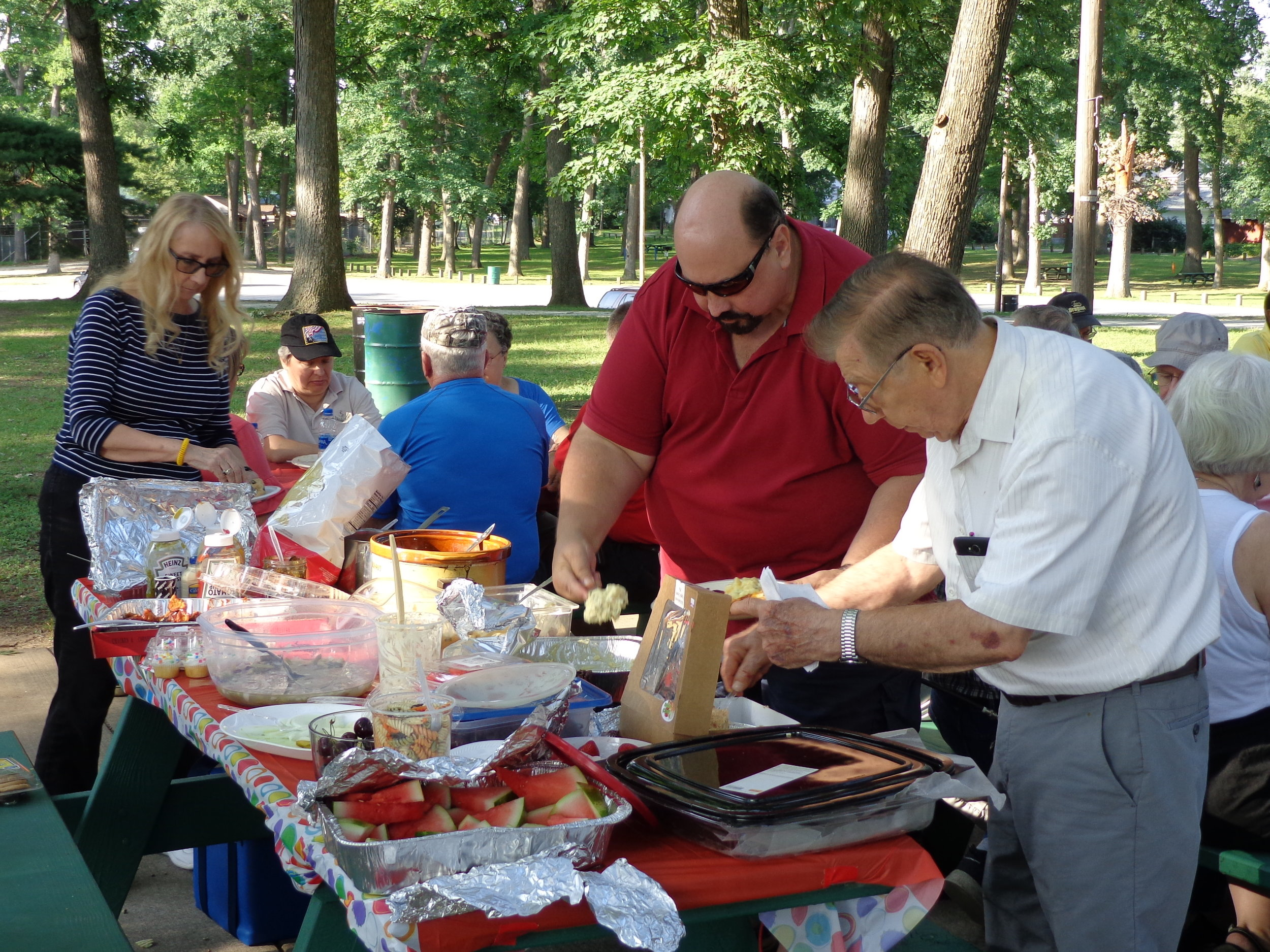 - Members Dan Caesar NI9Y, Jeff Wynegar KA9TOC and June Hill KC9IIC helping themselves to the many goodies on the food table.