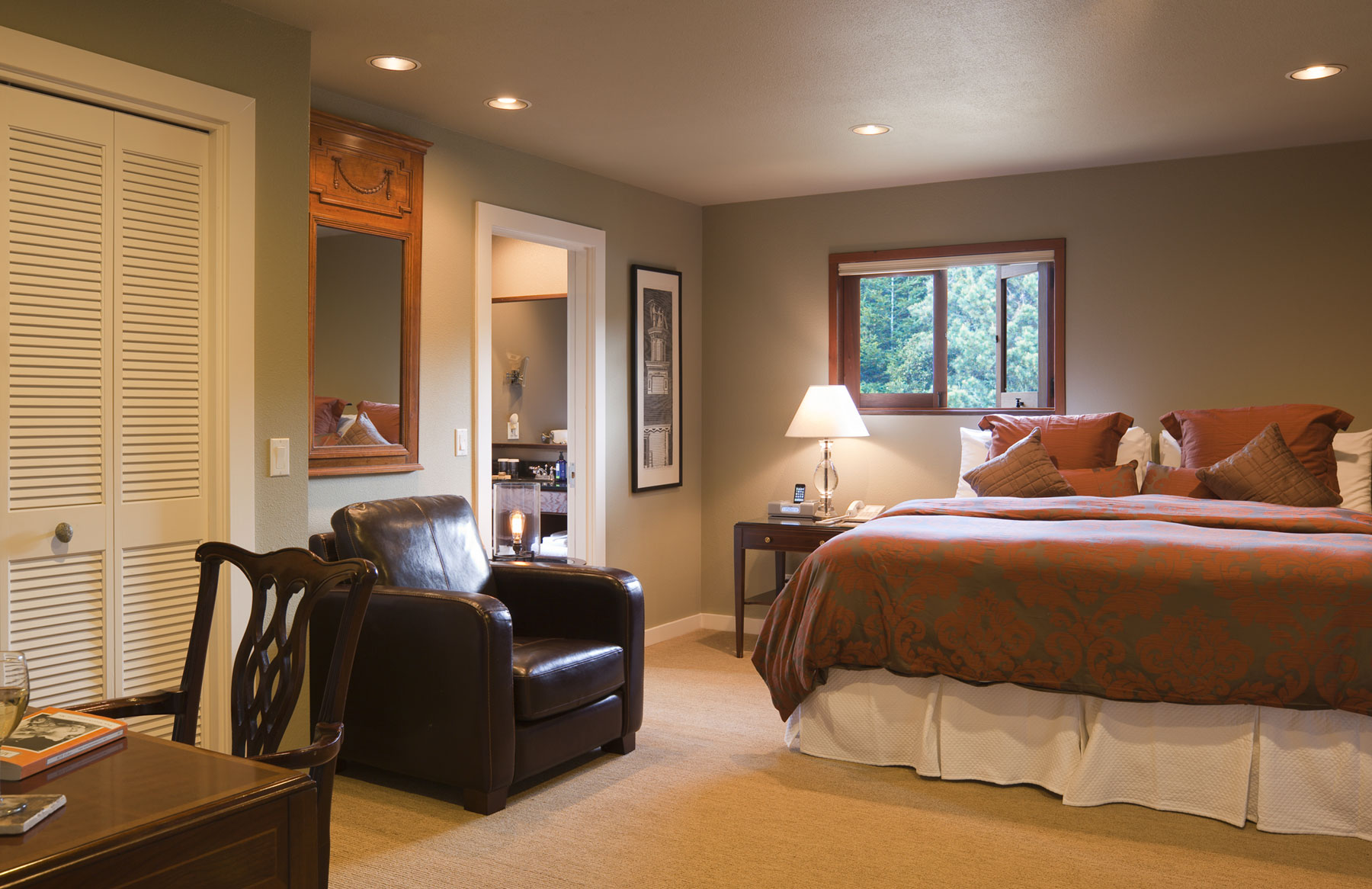 The second room in the Meadowview suite contains a king bed, desk, and leather chair.
