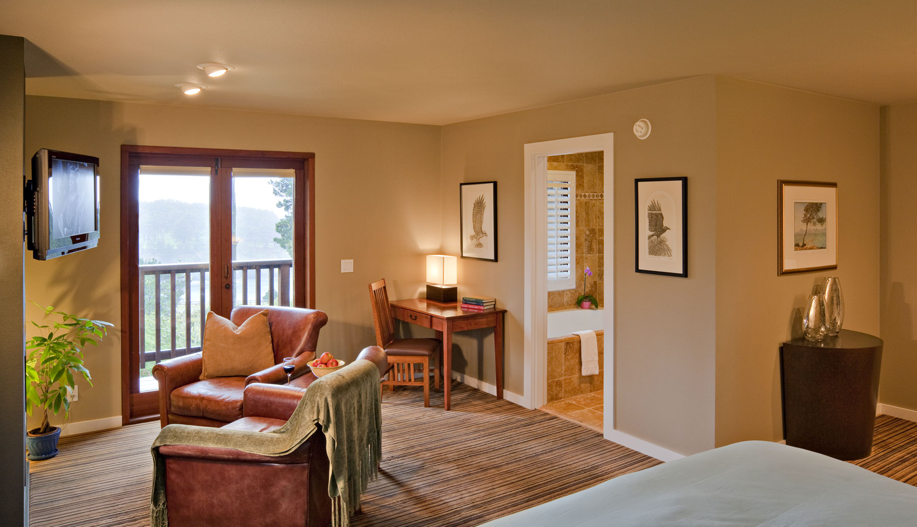 The Osprey room with French doors onto private blacony, leather seating in front of flat screen TV