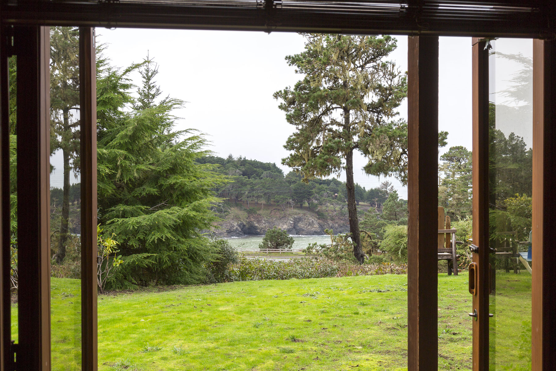 A view out to the lawn and the ocean in the distance from the Manzanita room