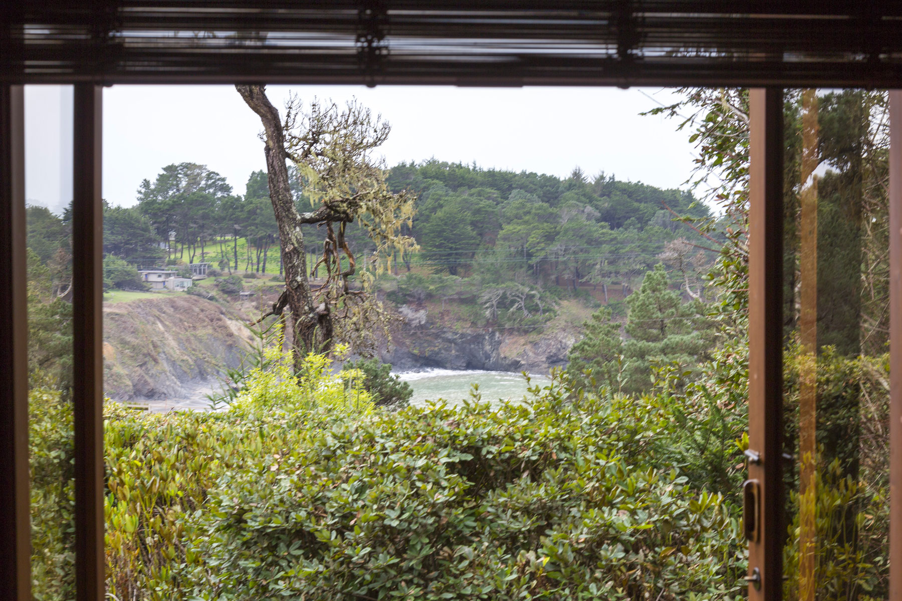The Madrone room window looks out to a view of the ocean cove