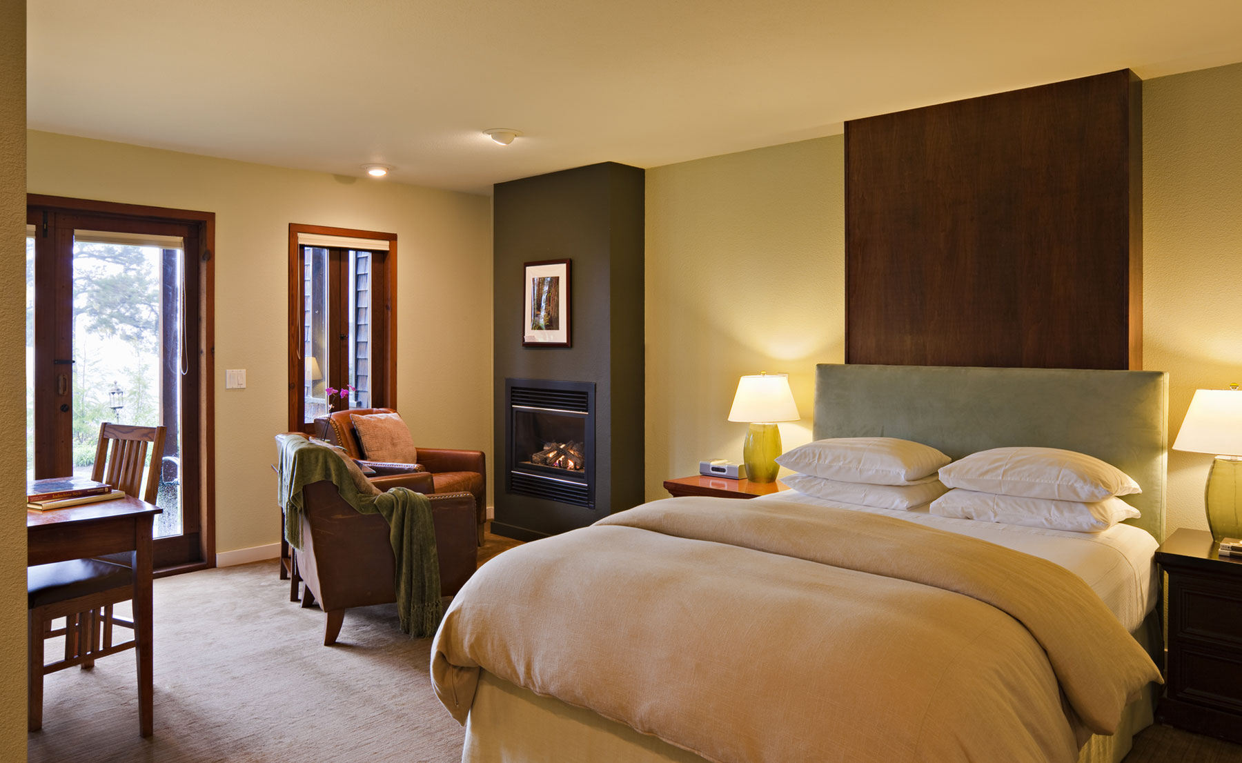 The ADA Accessible Redwood room with Queen bed, desk, French doors, and leather seating around a fireplace