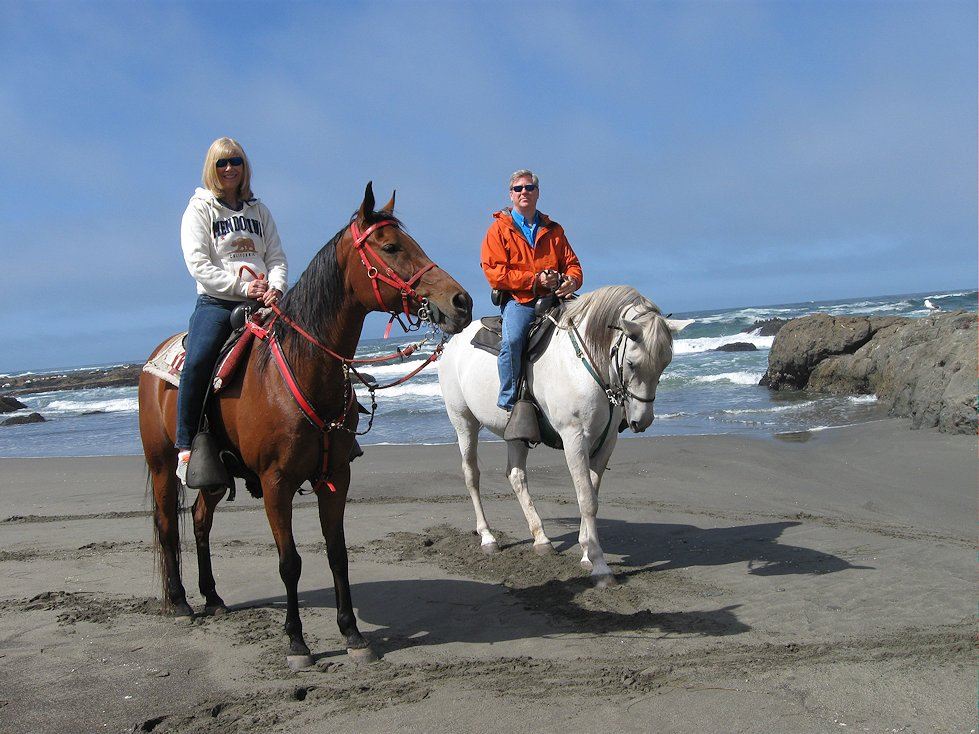 A couple on horseback on a beach north of Mendocino, California.