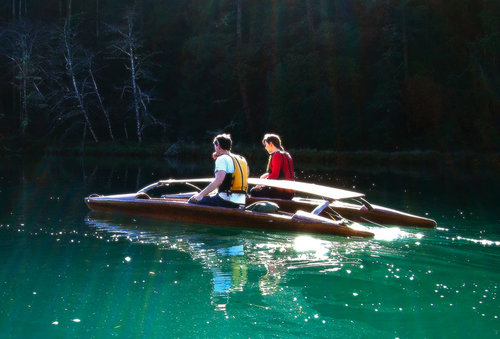 A couple share a two-part canoe on a green river float by forest.