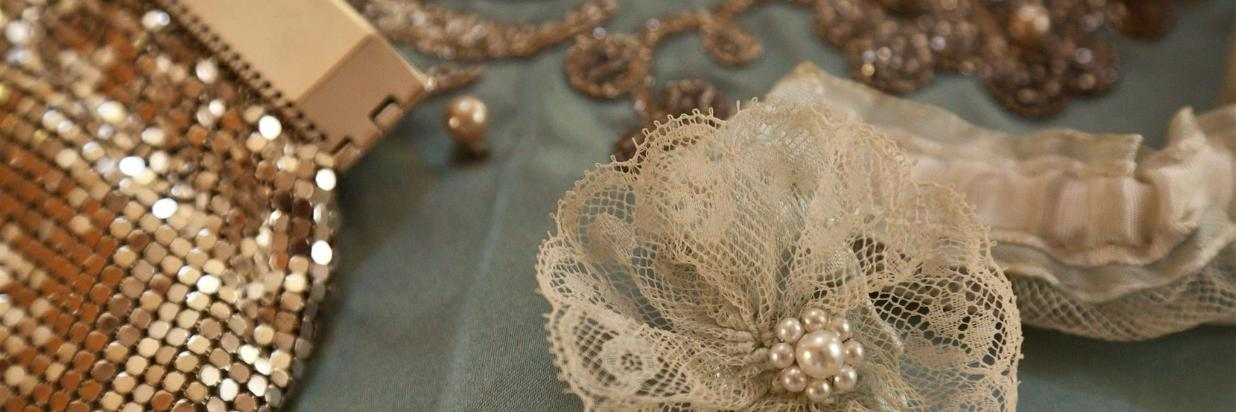 A close up of a shimmery purse, a lace and pearl hair accessory, and jewelry.