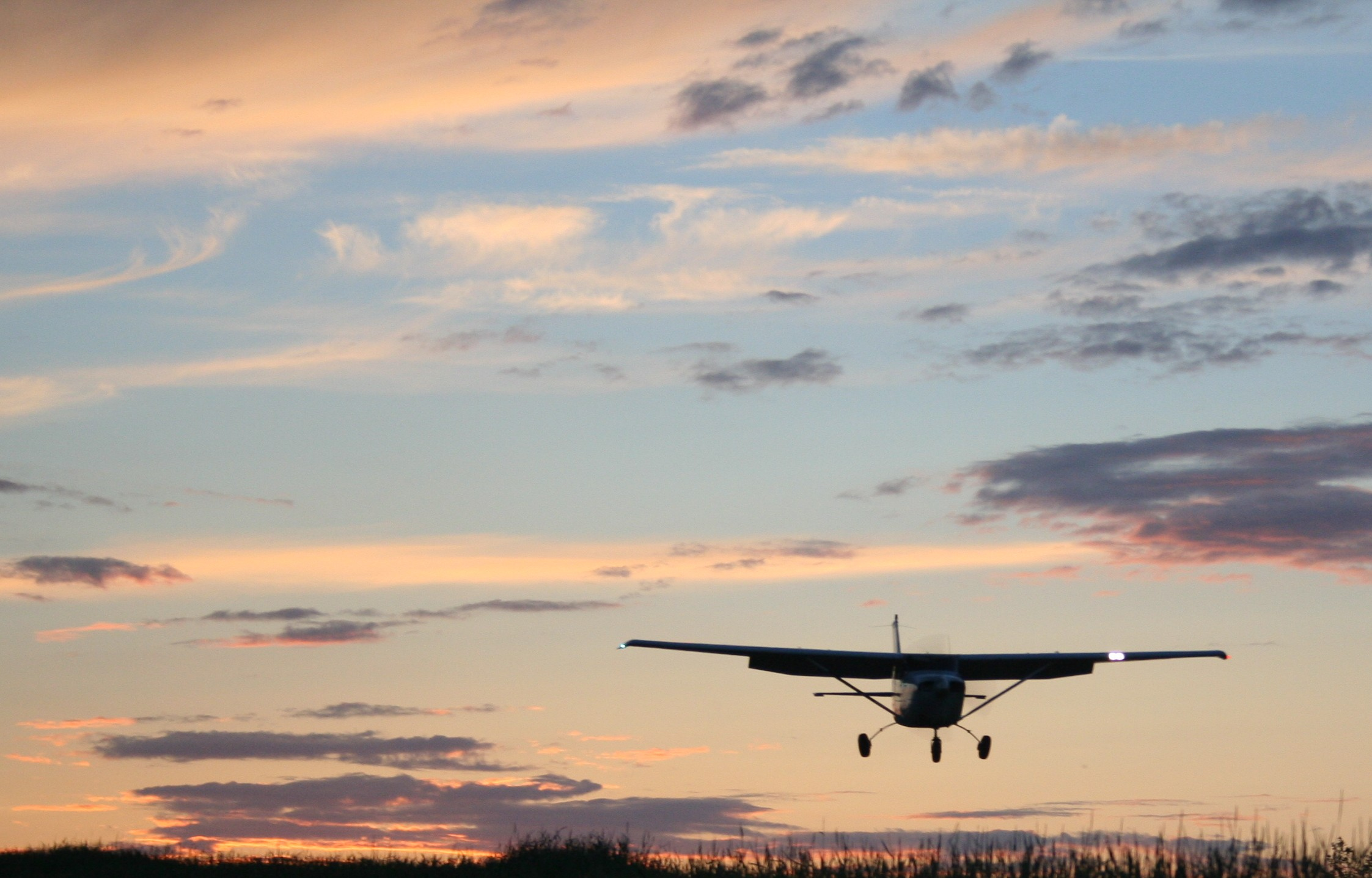 A small plane landing with a sunset streaked sky behind it.