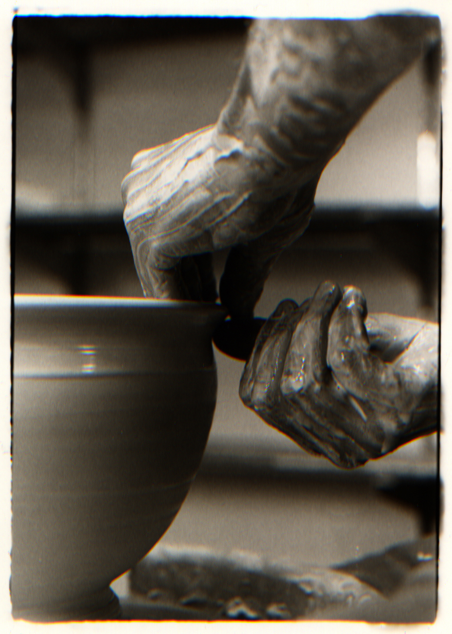 sepia photo of potters hands shaping a large bowl