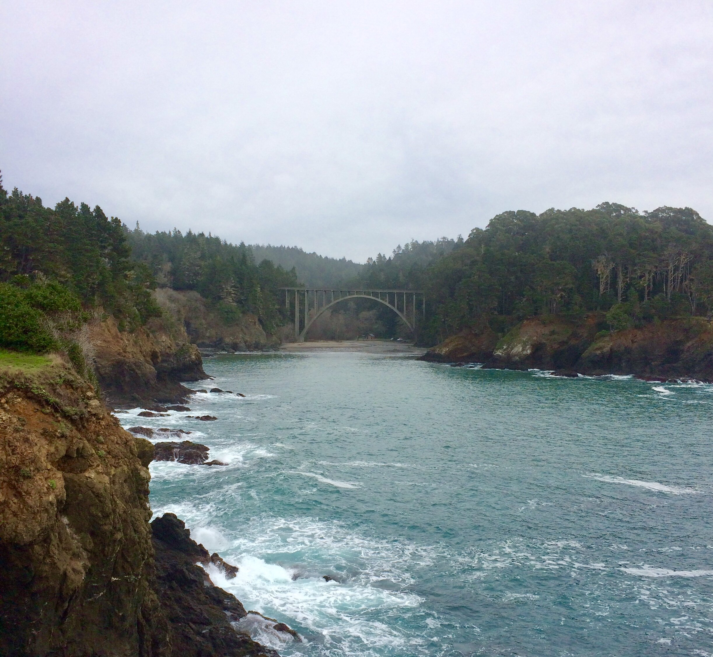 The view from the park's headlands back toward the beach and the charming bridge.
