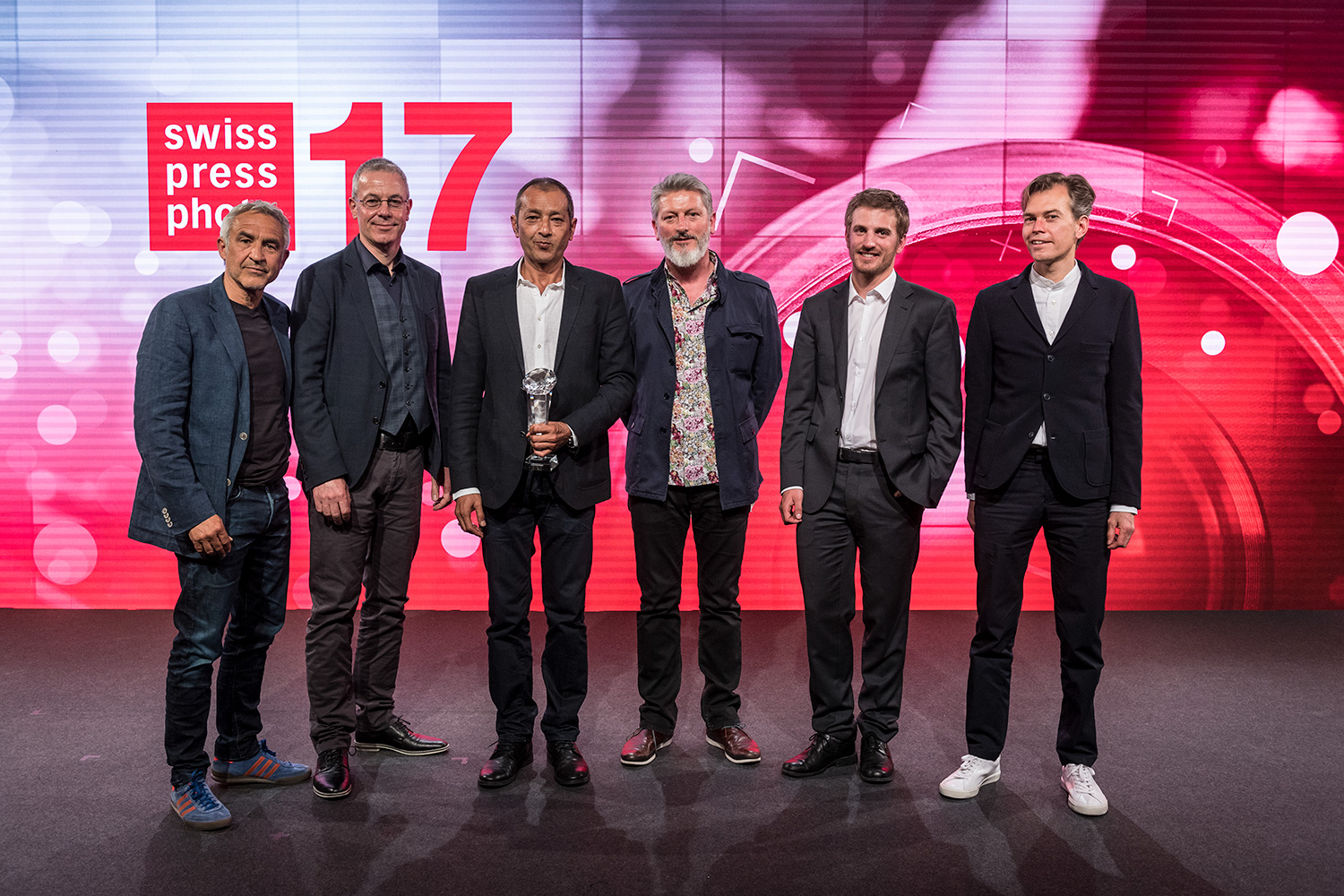 The award-winning photographers pose on the stage, from left to right, Rolf Neeser, Urs Bucher, Zalmai Ahad as Photographer of the Year, Mark Henley, Anthony Anex and Stephan Rappo, on Wednesday, April 26, 2017, at the award ceremony for the Swiss Media Prize Swiss Press Award 17 at the Hotel Bellevue in Bern. (KEYSTONE/Alessandro della Valle)