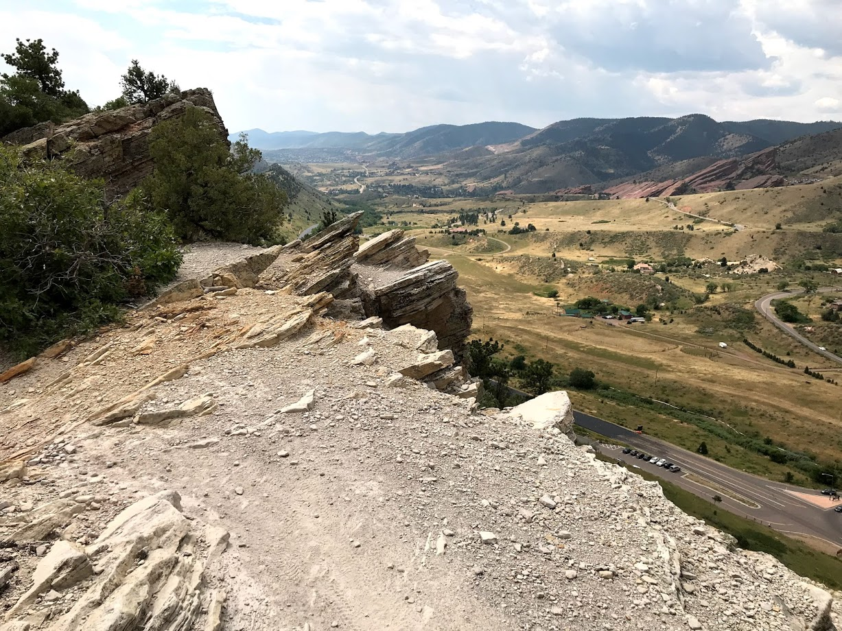 Standing atop a hogback with a striking view of the Front Range of the Rocky Mountains. The sedimentary beds along the hogback are steeply tilted and form a prominent linear ridge. As these layers erode and fall away, they expose beautiful glimpses into the past. Evidence of ancient waterways and an inland sea. Fluvial deposits, ocean ripples, claystone churned by ancient organisms, volcanic ash, and even dinosaur tracks and bones.