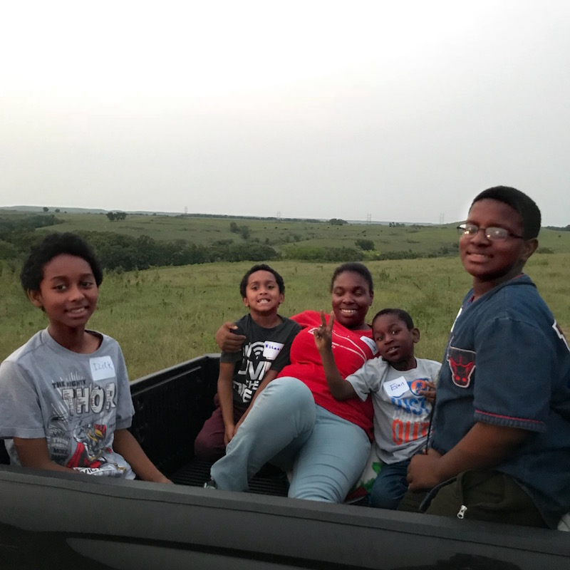 Participants in a meteor shower watch party ride to the top of a hill in the back of a pickup truck. This event took place at Bird Runner Wildlife Refuge on August 11, 2018, and more than 67 people attended. It was co-sponsored by Audubon of Kansas, the Junction City Juneteenth Community Association, and Prairie Heritage, Inc.