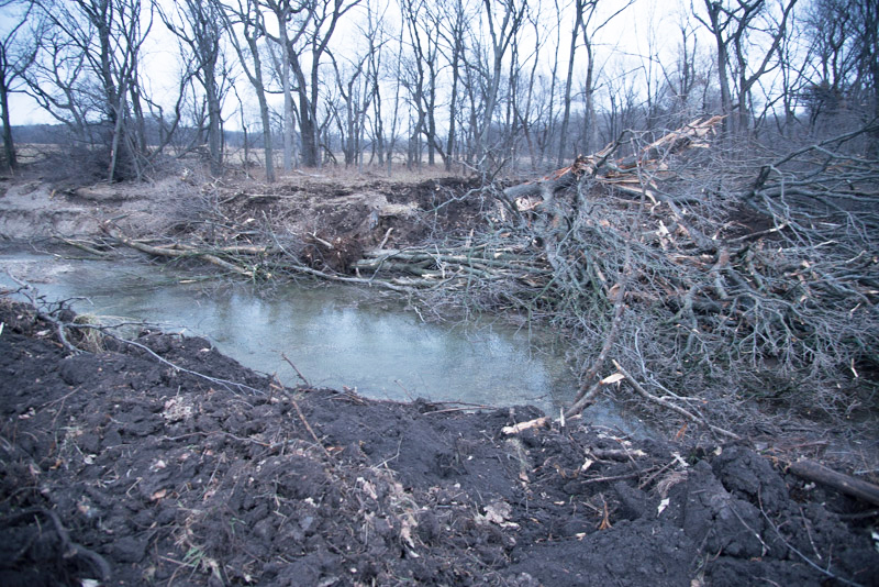 Streams that fall through the cracks of regulatory oversight are still being destroyed. In this case, a meander of a Kansas stream is cut off and a new channel is dredged along the edge of the nearby hill after all of the riparian forests were cleared (soon after this photo was made).