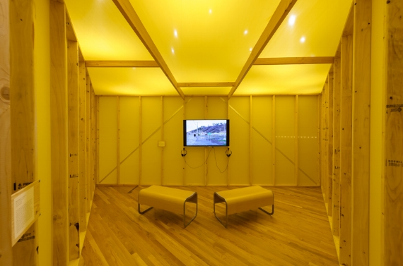 Pablo Helguera, School of Panamerican Unrest Banner, 2006. Installation view, AD&A Museum, UC Santa Barbara. [image description: interior of a room where everything is yellow, at the centre is a video screen playing footage of a landscape, in the foreground are two symmetrical benches on a wooden floor]