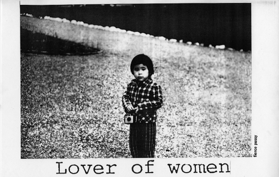 Poster by fierce pussy. Courtesy of Leslie Lohman Museum of Gay and Lesbian Art, and Fierce Pussy. [image description: black and white photograph of little girl in checkered shirt, she holds a camera, at the base of the image there is the text: Lover of Women]
