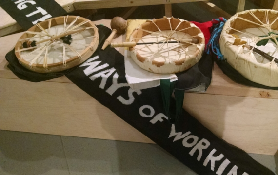 {image description: on a wooden bench, is a banner in black with white text, it says: Ways of Working, on it are three traditional drums with drum sticks]