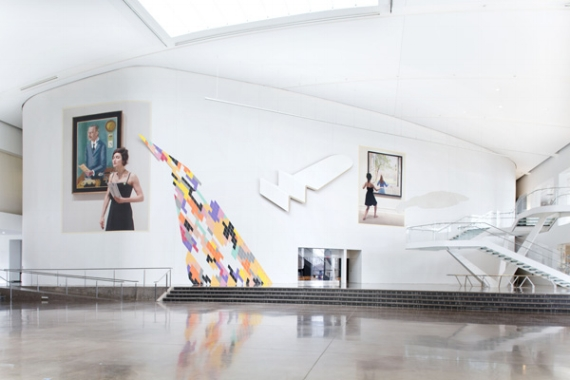 Anna K.E., Profound Approach and Easy Outcome, 2017. (installation view). 140 ft. x 27 ft. Courtesy the artist. Photo by Hai Zhang. [image description: on huge curving wall in foyer space there are a number of images against the white wall, left, there is a woman holding something, with a portrait of a man behind her, In the middle there is a jigsaw like distortion of different colors, and on the right there is a woman looking in a mirror]