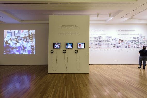Suzanne Lacy and Pilar Riaño-Alcalá. Skin of Memory, 1999; installation view, The Schoolhouse and the Bus, 2017. Courtesy of AD&A Museum. [image description: on the left footage of a parade plays projected on to a white wall, in the centre are three small monitors, on which footage plays, on the right is a timeline with indecipherable images on a white wall]